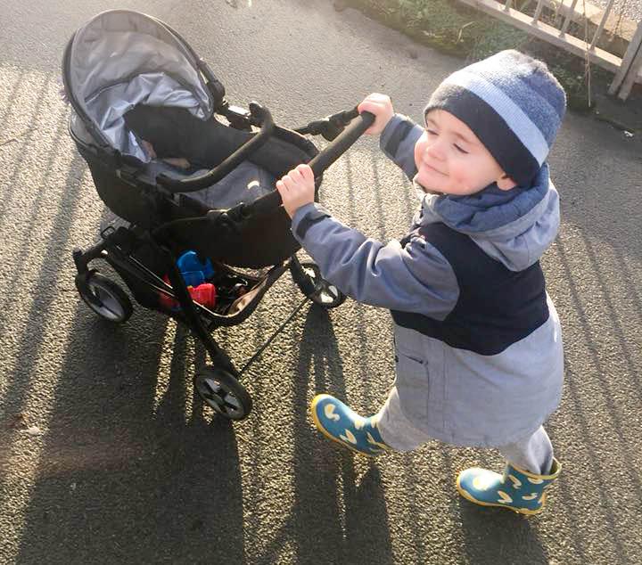 Little-boy-wearing-wellies-hat-ushing-dolls-pram