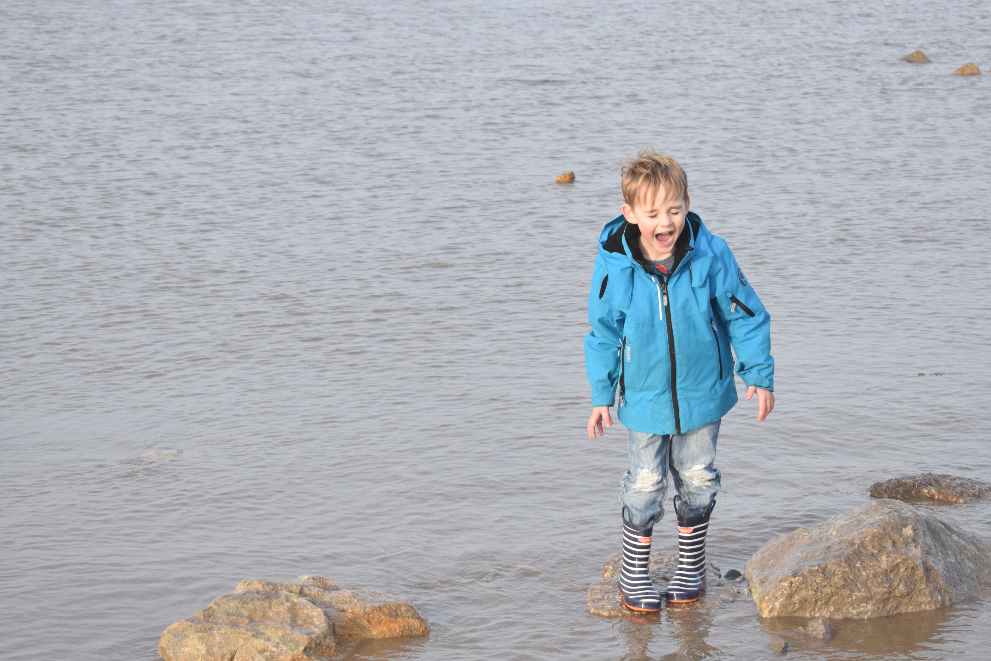 Boy jumping in the sea wearing stripey wellies and blue coat