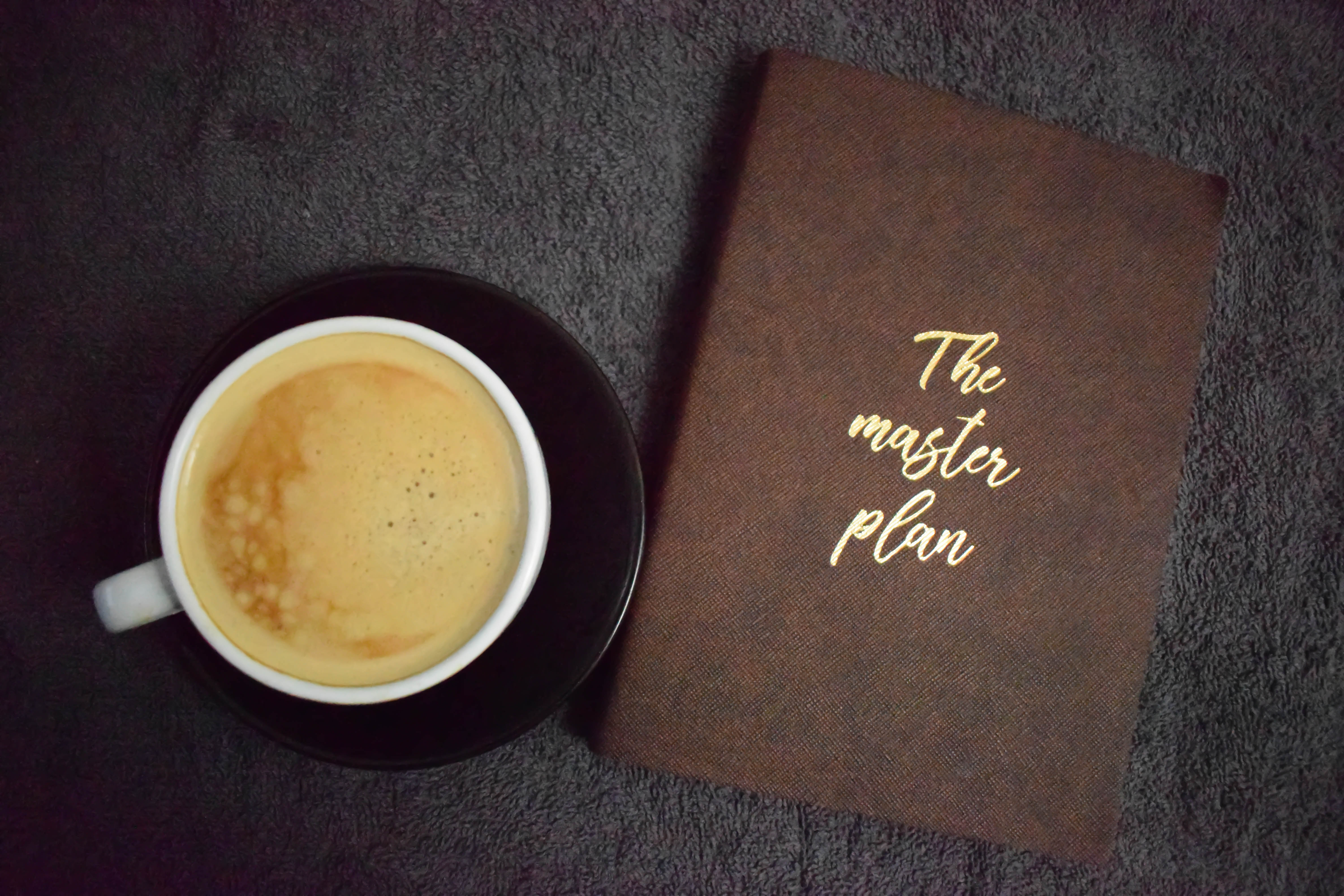 Cup and saucer of frothy coffee with notebook on dark grey background